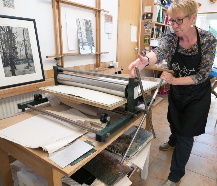 Linda in her studio using her etching press